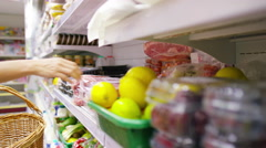4K Young woman putting food items into her basket at the grocery store Stock Footage