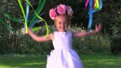 Happy girl in flower wreath playing with colored ribbons in the summer park Stock Footage