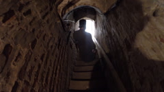 Stock Video Footage of Silhouette of a man coming down the narrow dark corridor ancient stairs