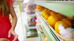 4K Young woman putting food items into her basket at the grocery store - stock footage
