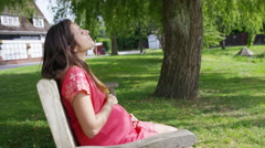 4K Portrait of young pregnant woman relaxing in the park with hand on her belly Stock Footage