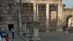 Time lapse of tour groups sitting and moving around synagogue ruins. Cropped. Stock Footage
