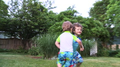 """Two young boys play """"ring around the rosie"""" in the backyard. - stock footage"""