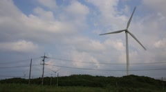 Beautiful landscape with windmills and vehicles on the road in Jeju island Stock Footage