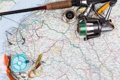 fishing tackles - rod, reel, line and lure on map - stock photo