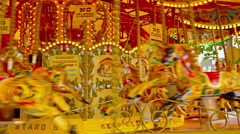 People entertaining on a carousel moving with colorful wooden horses, London Stock Footage