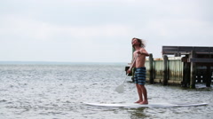 Young fit male on stand up paddle board - stock footage