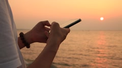 Man's hands using smart phone on beach against beautiful sunset - stock footage