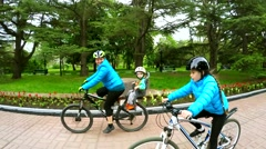 Active Mother With Children Cycling In Green Park Stock Footage