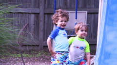 Two young boys smile while being sprayed with sprinkler. - stock footage