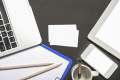 Laptop, stationery, mobilephone, and business card on black board top view Stock Photos