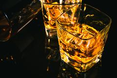 Top of view of glass of whiskey near bottle on black table with reflection Stock Photos