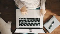 Woman sitting on the floor and working on a laptop, top view Stock Footage