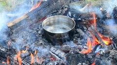 Putting steel saucepans into open fire outdoors for cooking food Stock Footage