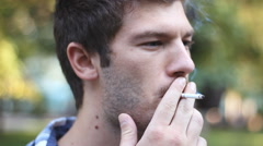 Young hipster Rebel man smoking cigarettes in the park - stock footage