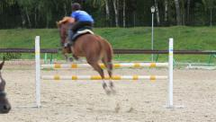 Horse riders jumping over a hurdle Stock Footage