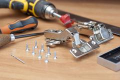 On the table are two furniture hinges and screws. In the background a drill, - stock photo