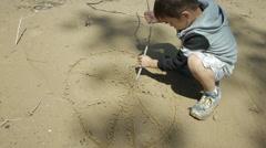Boy writes on wet sand Stock Footage