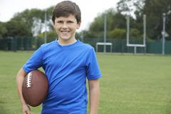 Portrait Of Boy Holding Ball On School Football Pitch Kuvituskuvat