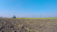 The tractor works the soil disc cultivator.It weighs on the grille of a car tire - stock footage