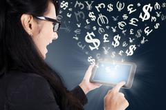 Businesswoman making money online with tablet - stock photo