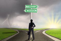 Businesswoman with road sign to recovery or recession finance Stock Photos