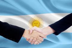 Handshake and argentina flag background - stock photo