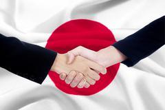 Handshake with a japanese flag background - stock photo