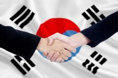 Handshake with south korean flag background - stock photo