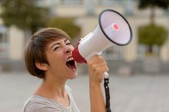 Young woman yelling into a megaphone or bullhorn Kuvituskuvat