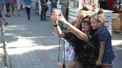 Mather with her daughters making self photo on the street Stock Footage