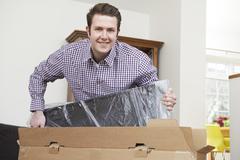 Man Unpacking New Television At Home Kuvituskuvat