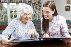 Grandmother Looking At Photo Album With Teenage Granddaughter Stock Photos