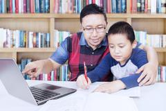 Man teach a boy in library - stock photo