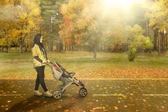 Mother with carriage going for a walk in - stock photo