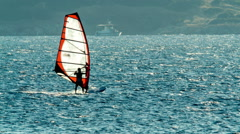 Wind surfing,surfer in the open sea,camera pan across. - stock footage
