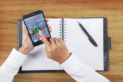 Worker using app of windows 10 on cellphone - stock photo