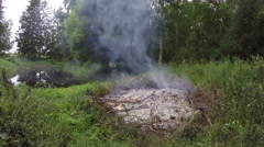 Fire burning on a pond shore, 4K Stock Footage