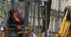 Driver Man in Orange Workwear in Cabin Of Yellow Excavator Machine Stands Scoop Stock Footage