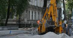 Worker Man in Orange Workwear People are Walking by Street Yellow Excavator is Stock Footage