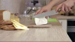 A man is slicing goat cheese with knife on the kitchen Stock Footage