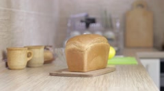 A man is cutting bread with knife (on the kitchen) - stock footage