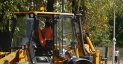 Worker in Orange Workwear Driver in Cabin of Yellow Excavator Flasher on its Stock Footage