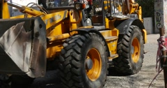 Yellow Excavator Turns And Leaves Road Repair People are Walking by Street Stock Footage