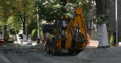 Workers in Orange Workwear Are Paving The Road Yellow Excavator with Flasher is Stock Footage