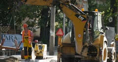 Workers in Yellow Workwear And Safety Helmets are Holding the Loader Hunging on - stock footage