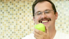 Adult man eating a green apple with pleasure. Stock Footage