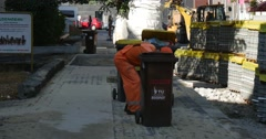 Worker in Yellow Wokwear Puts The Garbage to The Wastebaskets Pallets with Stock Footage