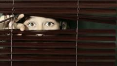 Brown-eyed girl looks through dark Venetian blind, is startled Stock Footage