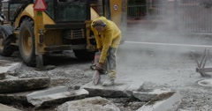 Man Worker in Yellow Workwear is Grinding The Blocks of Concrete by Grinding Stock Footage